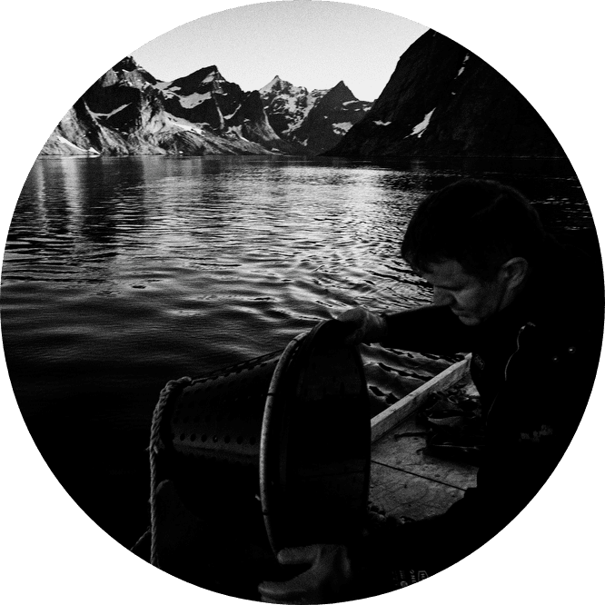 Black and white image. A man on the dock with water and mountains in the background.